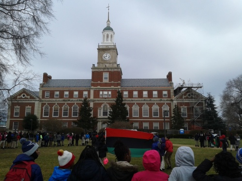 Middle School students holding the Pan-African flag standing in the center of a man-made circle formed by their peers.