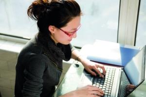 Asian woman sitting using laptop